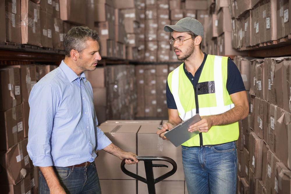 Warehouse manager talking with worker in a large warehouse.jpeg