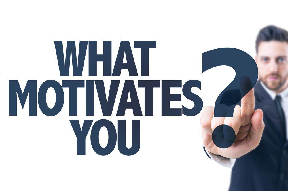 Business man pointing the text What Motivates You?.jpeg