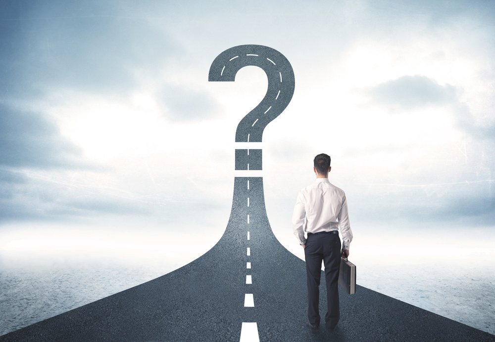 Business person looking at road with question mark sign concept.jpeg