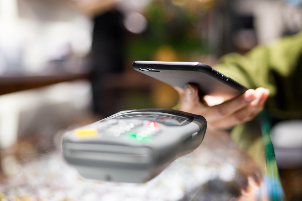 Woman paying with smartphone by NFC.jpeg
